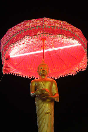standing golden buddha statue under pink umbrella Stock Photo