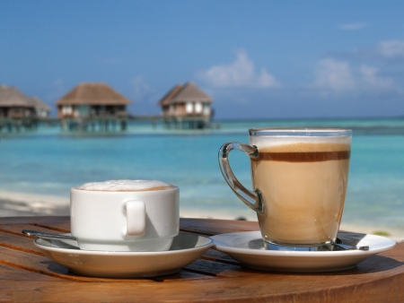 Coffee latte on beach in sunny day Stock Photo