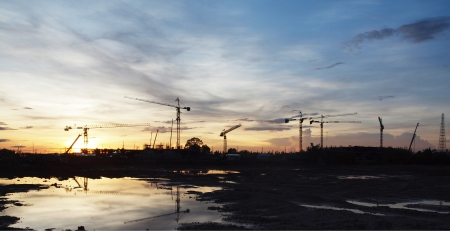 Many cranes in construction site in sunset