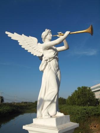 a sculpture of angel blowing golden horn