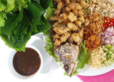 Thai food fried fish with herbal side dish photo