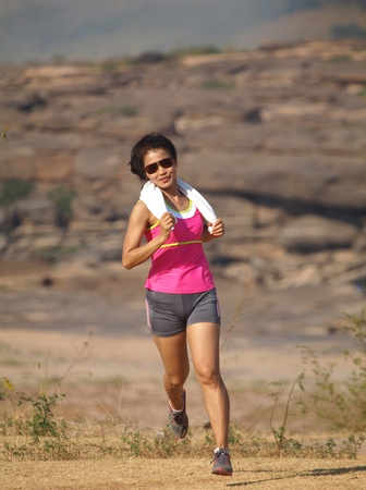 a woman running on the rocky road photo