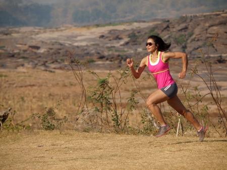 une femme courir sur la route rocheuse