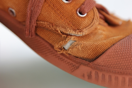 tatter: Tatter hole on old canvas brown shoe Stock Photo