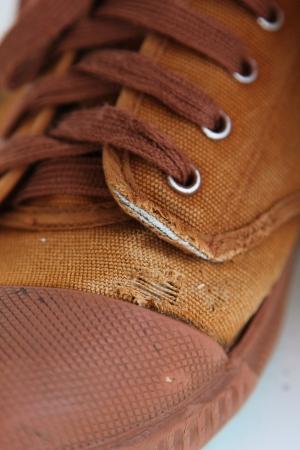 tatter: Agujero Tatter en el viejo zapato marr�n lona