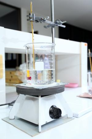 Beaker with water warming on hot plate in lab Foto de archivo