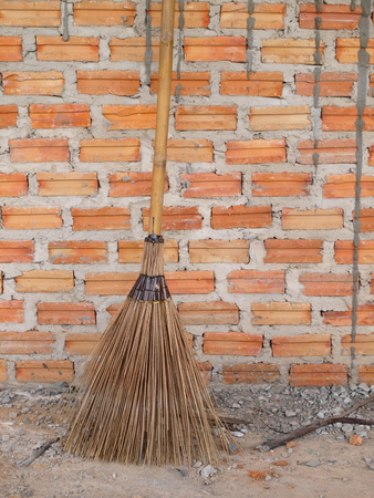 Wooden broom lay on brick wall photo