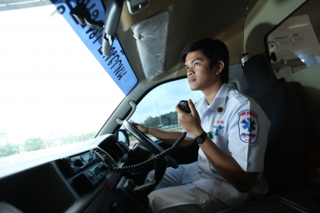 UBON RATCHATHANI, THAILAND – AUG 7, 2013 : Pornchai Kaotong on duty as a driver of ambulance contacts team with radio communication on Aug 7, 2013 in Ubon Ratchathani University hospital, Warinchamrab, Ubon Ratchathani, Thailand. Redakční