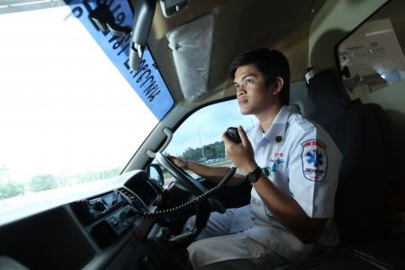 UBON RATCHATHANI, THAILAND – AUG 7, 2013 : Pornchai Kaotong on duty as a driver of ambulance contacts team with radio communication on Aug 7, 2013 in Ubon Ratchathani University hospital, Warinchamrab, Ubon Ratchathani, Thailand.
