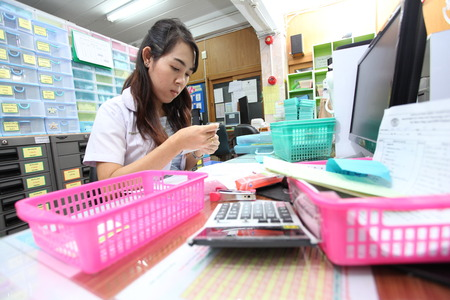 UBON RATCHATHANI, THAILAND – AUG 15, 2013 : Unidentified pharmacists prepare and checking drugs by the prescriptions in pharmacy department on Aug 15, 2013 in Sappasitparsong hospital Ubon Ratchathani, Thailand.