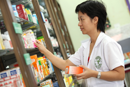 UBON RATCHATHANI, THAILAND – AUG 15, 2013 : Unidentified pharmacist checking drug on shelves in drug store on Aug 15, 2013 in Ubon Ratchathani, Thailand.