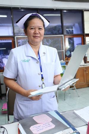 UBON RATCHATHANI, THAILAND – AUG 21, 2013 : Unidentified nurse holding patient profile chart on ward on Aug 21, 2013 in Sappasitparsong hospital Ubon Ratchathani, Thailand.