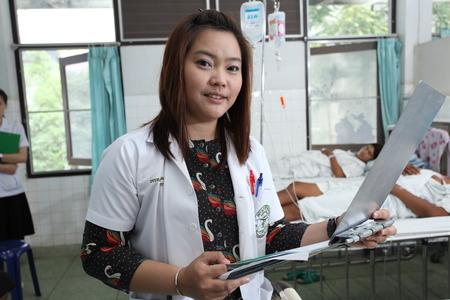 UBON RATCHATHANI, THAILAND – AUG 21, 2013 : Unidentified pharmacist holding patient profile chart on ward on Aug 21, 2013 in Sappasitparsong hospital Ubon Ratchathani, Thailand.