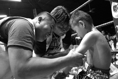 interstice: UBON RATCHATHANI, THAILAND – JUNE 14, 2003 : Staffs of boxing team take care of young Thai boxer during interstice of the round on June 14, 2003 in Wing21 Air Force Army, Ubon Ratchathani, Thailand. Editorial