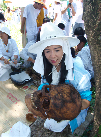 death head holding: UBON RATCHATHANI, THAILAND – APR 19, 2009 : Unidentified woman holding skull of unidentified corpse for grave clearing activity on Apr 19, 2009 in Ubon Ratchathani, Thailand