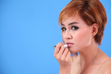 Portrait of Asian lady applying lipstick for herself photo