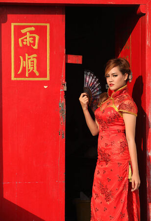 Woman in Chinese dress standing at the red door photo