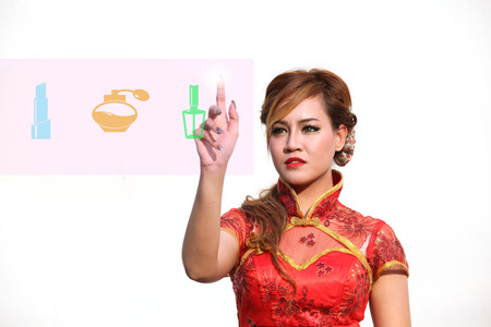 Woman in Chinese dress selects cosmetic on touch screen computer photo