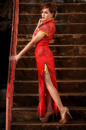 posa sexy: Donna in abito cinese in piedi sulle scale in posa sexy Archivio Fotografico