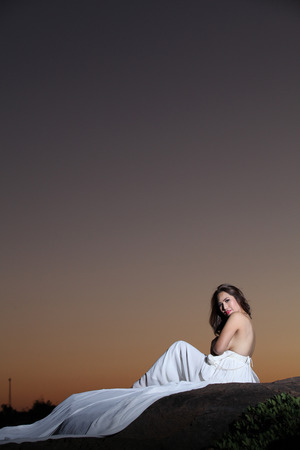 Young woman in white dress in sunset sky