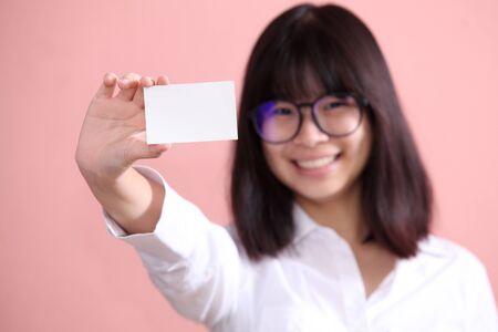 hoja en blanco: Muchacha asiática que sostiene la hoja en blanco Foto de archivo