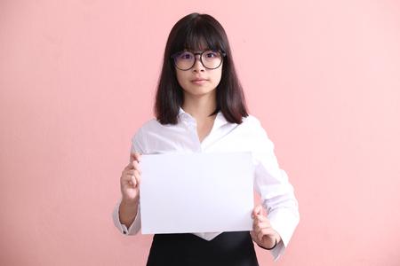 blank sheet: Muchacha asi�tica que sostiene la hoja en blanco Foto de archivo
