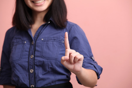 beautiful teen: Beautiful teen pointing finger pink background