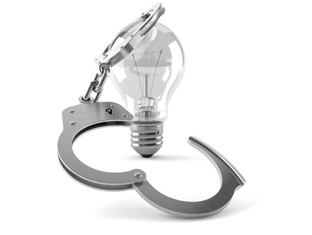 Light bulb with handcuffs isolated on white background Stock Photo