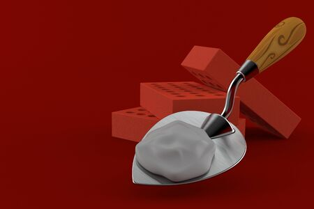 Bricks with trowel isolated on red background