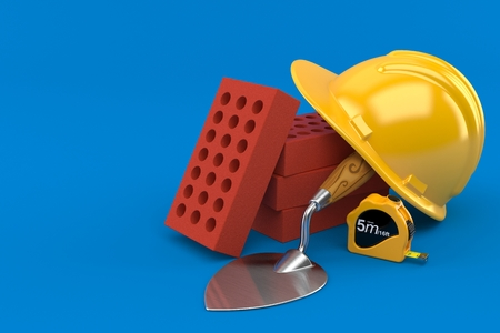 Bricks with trowel and hardhat isolated on blue background Foto de archivo