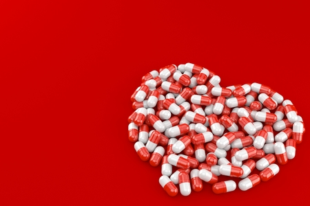 Heart symbol made from pills isolated on red background Stock Photo