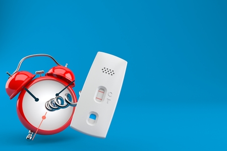 Pregnancy test with alarm clock isolated on blue background
