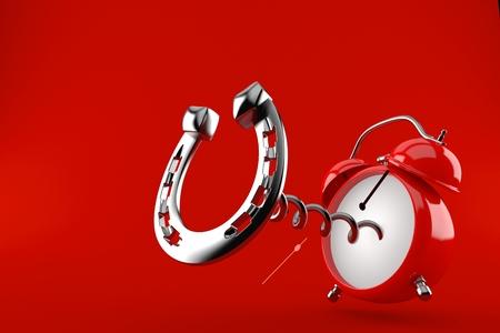 Horseshoe with alarm clock isolated on red background. 3d illustration Stock Photo