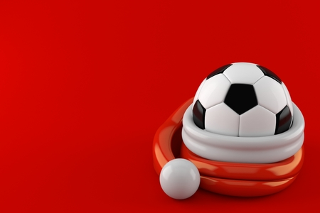 Soccer ball inside santa hat isolated on red background. 3d illustration Stock Photo