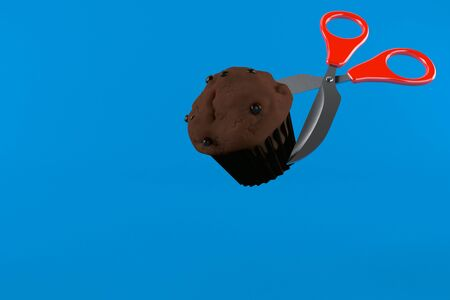 Muffin with scissors isolated on blue background. 3d illustration