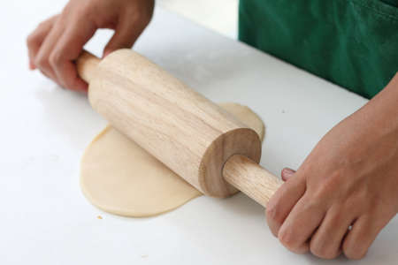 Human hands with rolling pin on table Stock Photo - 21020025