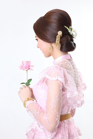chignon: elegant fashion asian woman posing with creative chignon hair-style and wearing pink thai dress,hold rose  Stock Photo