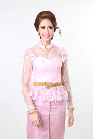 chignon: elegant fashion brunette woman posing with creative chignon hair-style and wearing pink thai dress  Stock Photo