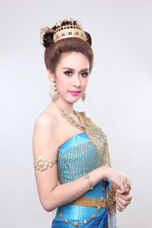 chignon: elegant fashion asian woman posing with creative chignon hair-style and wearing blue thai dress