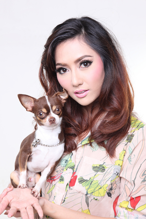 fashionable happy woman with cute chihuahua in hand photo