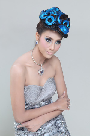 chignon: elegant fashion brunette Thai woman posing with creative chignon hair-style
