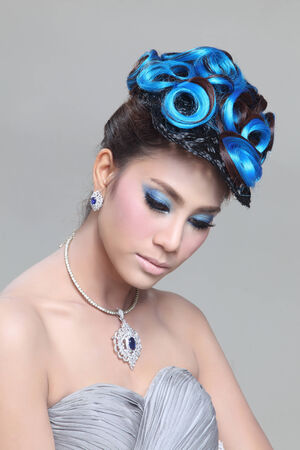 chignon: elegant fashion brunette Thai woman posing with creative chignon hair-style