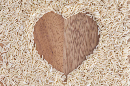 wooden boards: heart shape from rice on wooden background Stock Photo