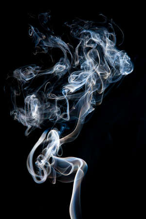 Colorful smoke abstract curly on black background Stock Photo