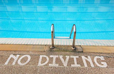 No diving sign at edge of swimming pool photo