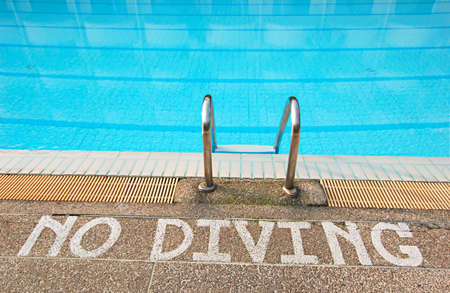 no diving sign: No diving sign at edge of swimming pool Stock Photo