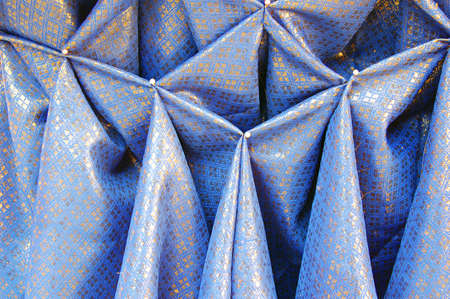 pleat: Blue and gold cloth with pinned pleats