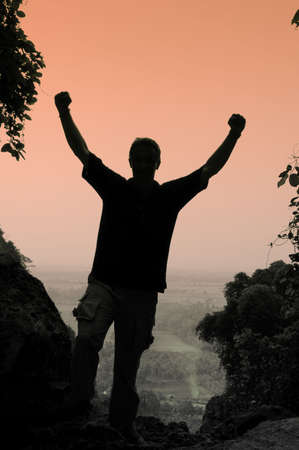 raised viewpoint: Silhouette of man at viewpoint with arms raised Stock Photo