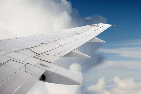 Aeroplane wing with cloudy blue sky behind Stock Photo - 3597418