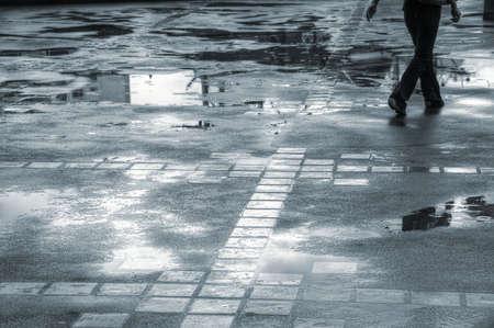 soak: Person walking through puddles on a wet sidewalk Stock Photo